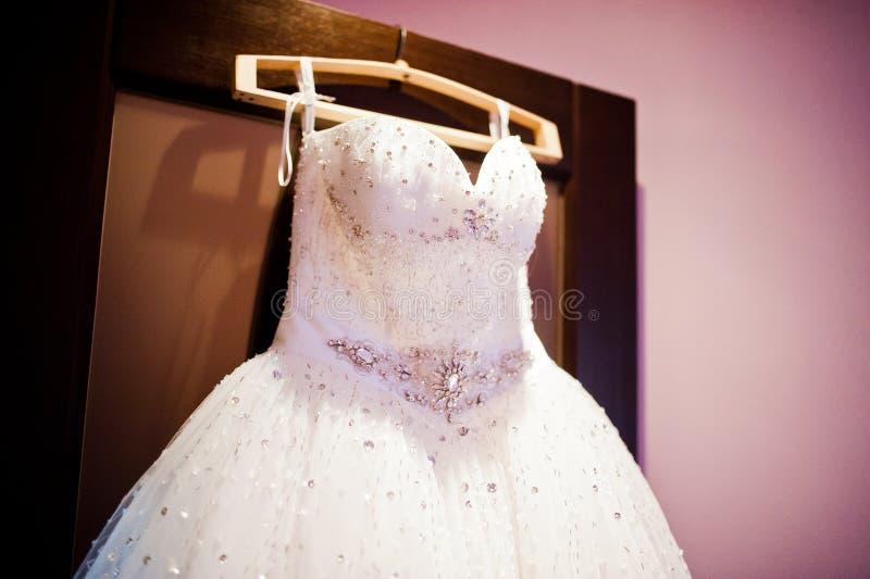 在挂衣架的壮观的婚礼礼服 库存图片