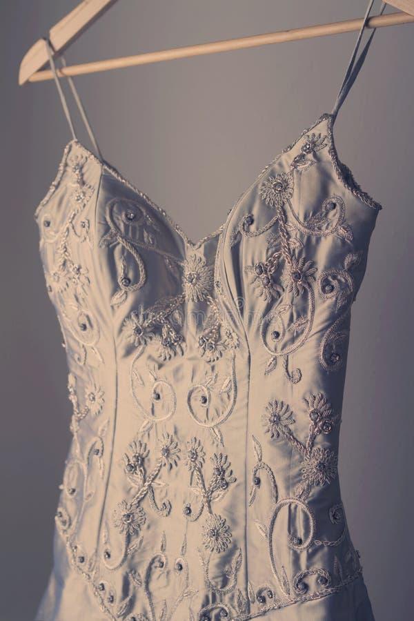 在挂衣架的惊人的葡萄酒婚礼礼服 库存图片
