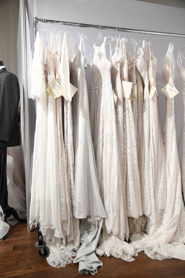 在挂衣架的新娘礼服在魅力新娘春天2020时尚介绍时 免版税图库摄影