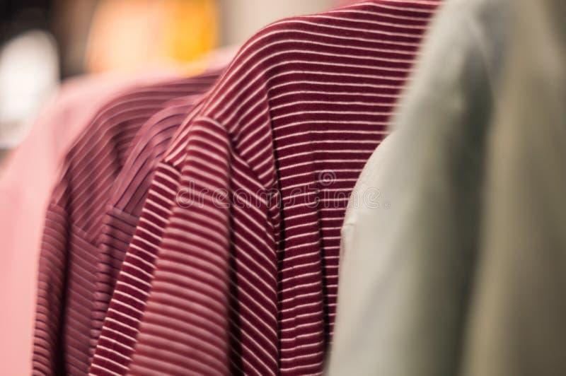 在挂衣架的红色镶边T恤杉在购物中心 库存图片