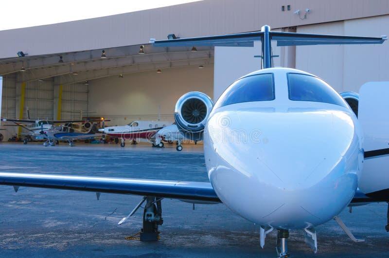 在挂衣架w飞机之外的私人公司喷气机 库存照片
