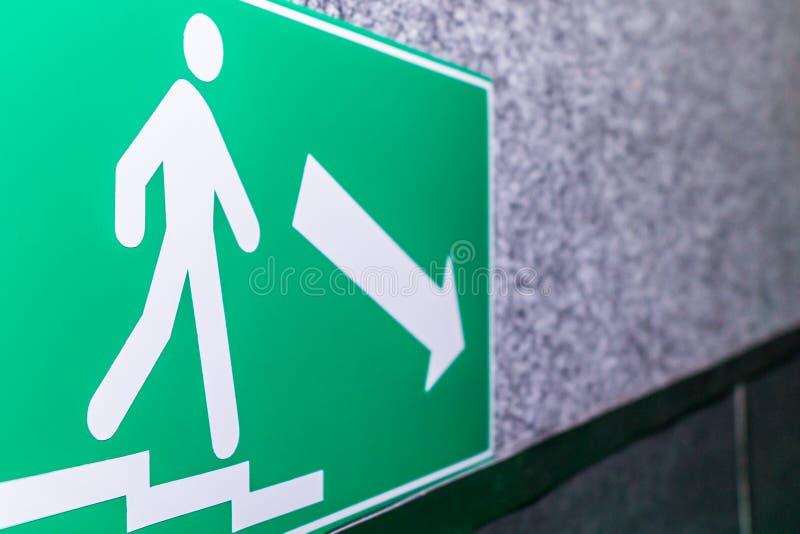 在指向往门的墙壁上的绿色标志箭头退出到一个安全的地方在火和紧急状态的情况下 图库摄影