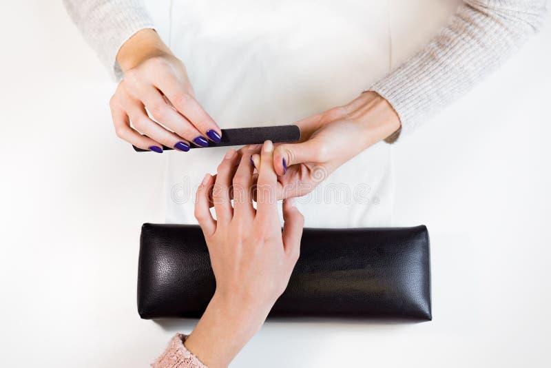 在指向手指的修指甲主要指甲锉工作 免版税库存照片