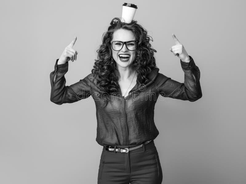 在指向隔绝的愉快的妇女在头的咖啡杯 免版税库存图片