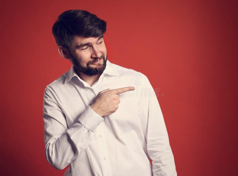 在指向fing的白色衬衣的愉快的享用的有胡子的事务 库存图片