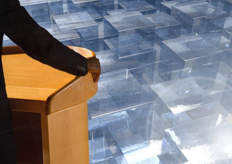在指挥台的商人发言在会议上与玻璃立方体 库存图片