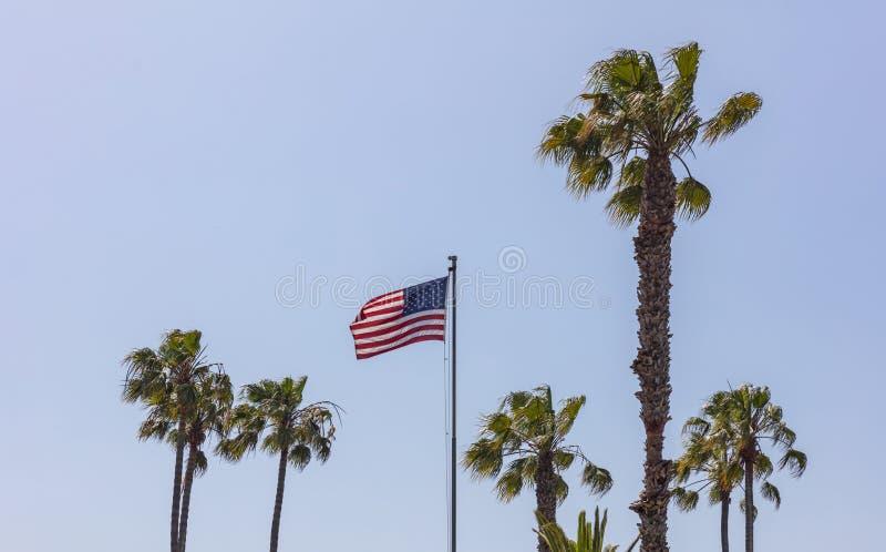 在挥动在天空蔚蓝背景的杆的美国旗子 免版税图库摄影