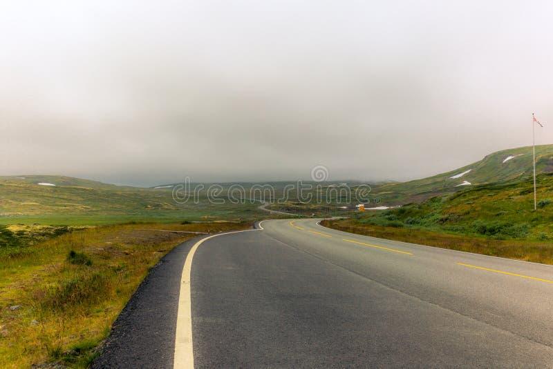 在挪威山- 2的一个长和弯曲道路 图库摄影