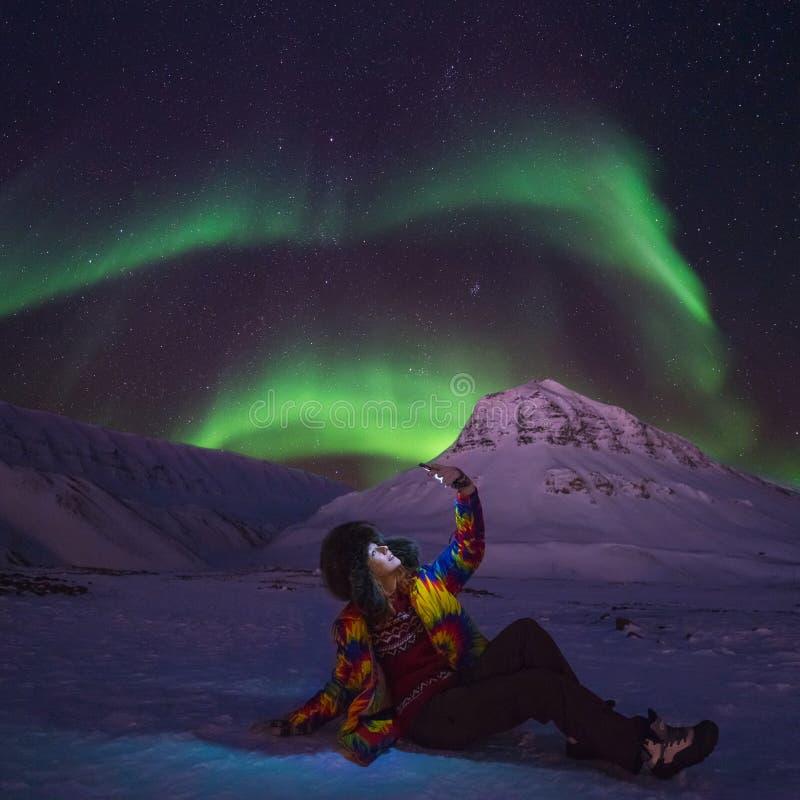 在挪威旅行博客作者女孩人斯瓦尔巴特群岛的北极北极光极光borealis天空星在朗伊尔城市月亮山 免版税图库摄影