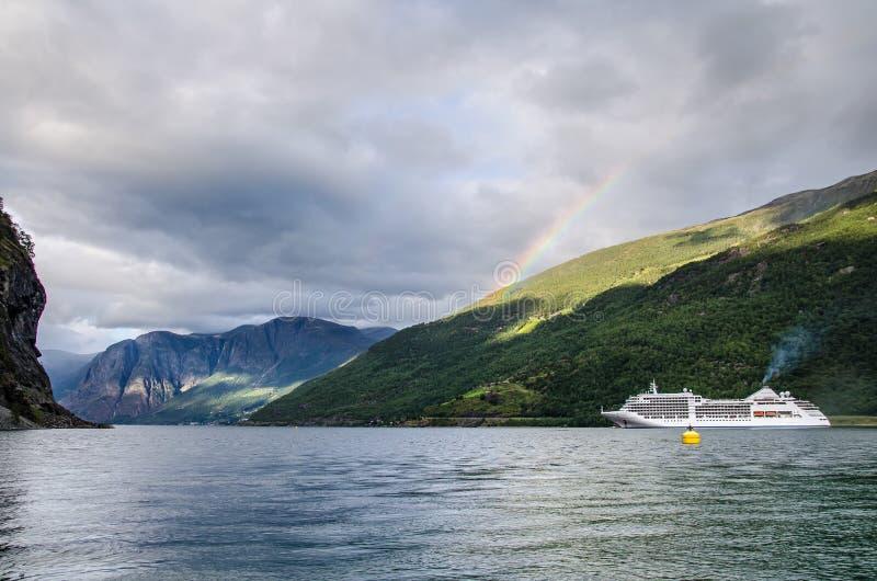 在挪威海湾的帆船有上面后边山的和彩虹和云彩 免版税库存照片