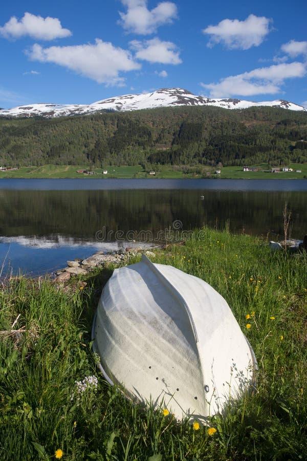 在挪威湖的岸的白色木小船在春天, snowly山在背景 图库摄影