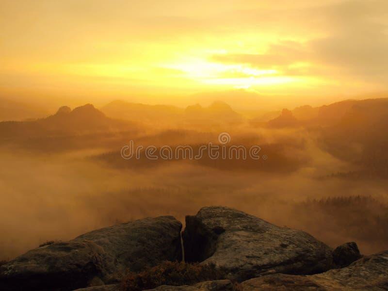 在捷克萨克森瑞士公园一座美丽的山的惊人的日出  从有雾的背景增加的岩石小山峰顶 库存照片