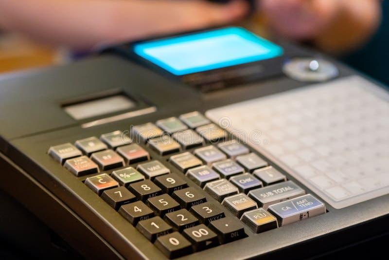 在接受的命令柜台安装的收款机从顾客 在电子收款机的销售人输入的数额  库存图片