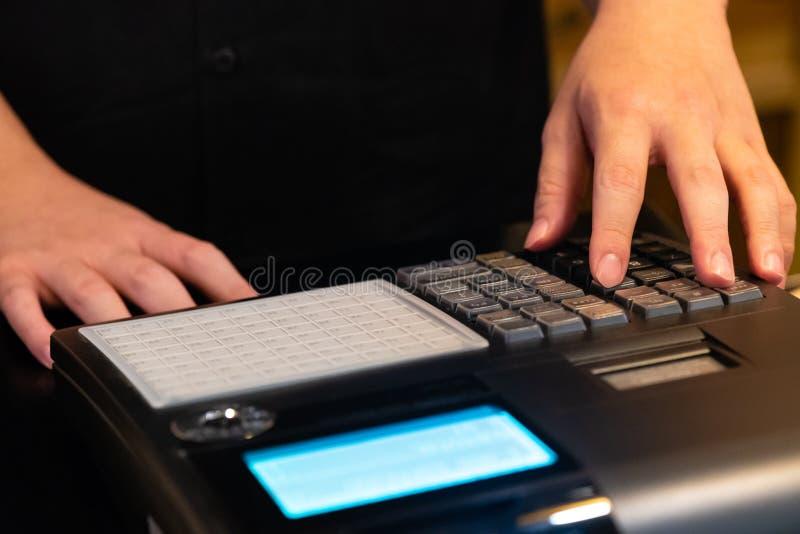 在接受的命令柜台安装的收款机从顾客 在电子收款机的销售人输入的数额  图库摄影