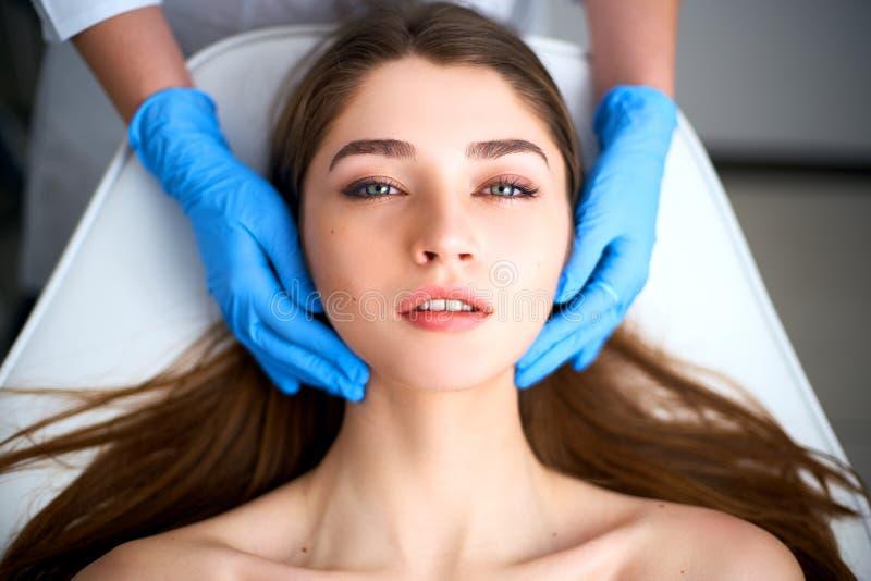 在接触可爱的妇女的面孔手套的美容师手 面部秀丽 有软的美丽的年轻女性使光滑 库存照片
