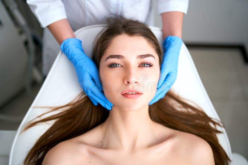 在接触可爱的妇女的面孔手套的美容师手 面部秀丽 有软的美丽的年轻女性使光滑 免版税库存照片
