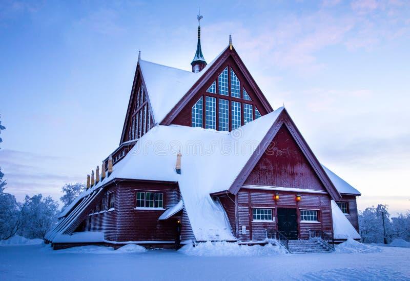 在接近黄昏的冬天期间积雪的教会 库存图片