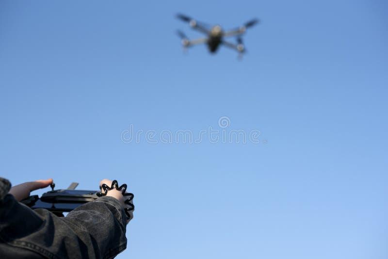 在控制寄生虫的遥远的控制器的妇女的手 寄生虫飞行 免版税库存图片