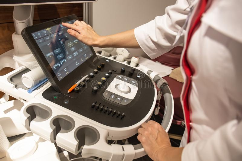 在控制板的医生手与医疗在诊所的超声波诊断设备键盘  库存照片