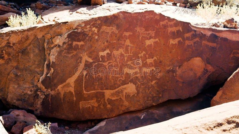 在推菲尔泉考古学站点,纳米比亚的史前刻在岩石上的文字 图库摄影