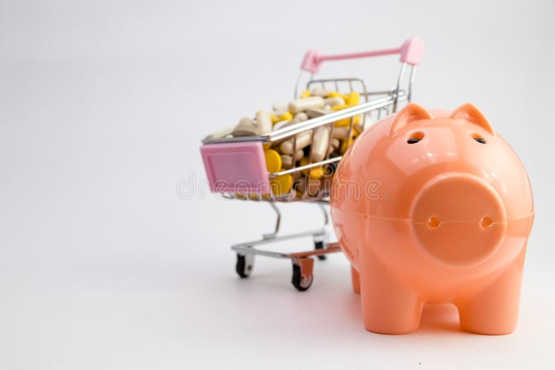 在推车的疗程 充分手推车药物和医学药片 Piggybank和金钱塔配药花费的概念 库存图片