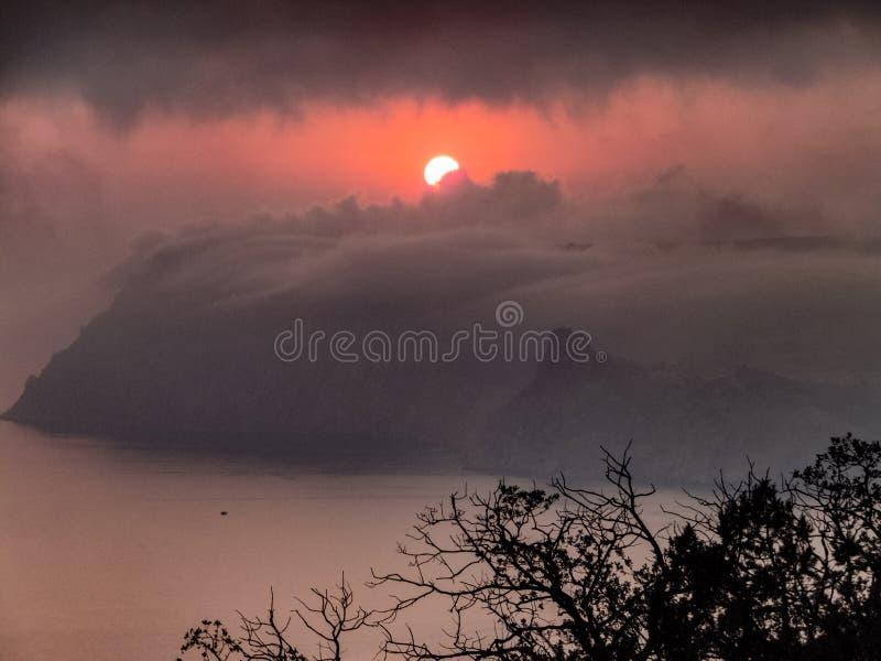 在掩藏在云彩的山的红色日落 免版税库存照片