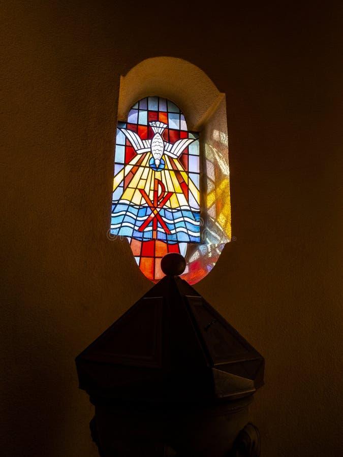 在描述圣灵作为鸠和Christogram的洗礼盘的覆盖物的污迹玻璃窗在教会里 免版税库存照片