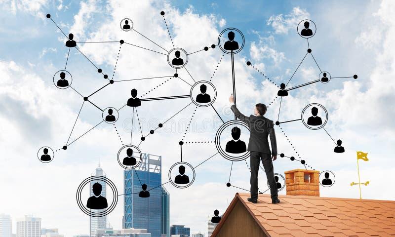 在提出网络和连接概念的房子屋顶的商人 混合画法 免版税图库摄影