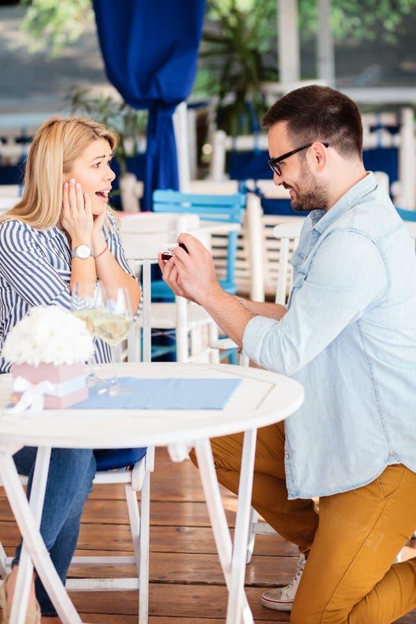 在提议的惊奇的和非常愉快的年轻女人由她的男朋友以后 免版税库存图片