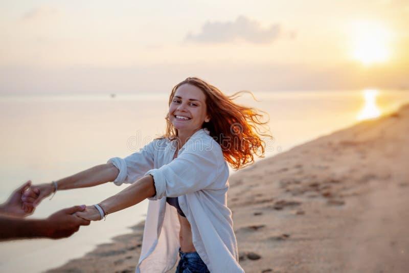 在握在海滩的爱旋转的美好的年轻夫妇手在日落在蜜月假期旅行期间 免版税库存照片