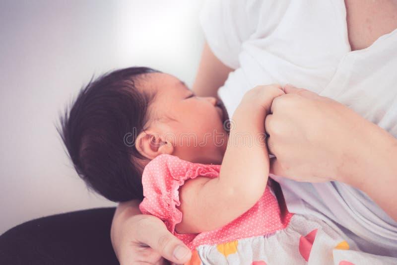 在握婴孩手的母亲手上的特写镜头,当母亲哺乳时 库存图片
