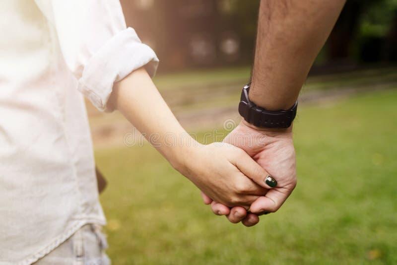 在握手和走在公园的爱的愉快的浪漫夫妇 免版税库存图片