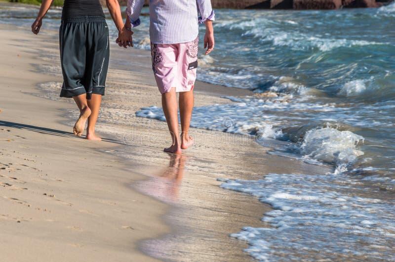 在握手和走在冬天季节的海滩的爱的夫妇 库存图片