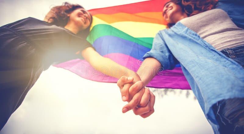 在握手的爱的美好的女性年轻女同性恋的夫妇和彩虹旗子,LGBT社区,平等权利的标志, 图库摄影