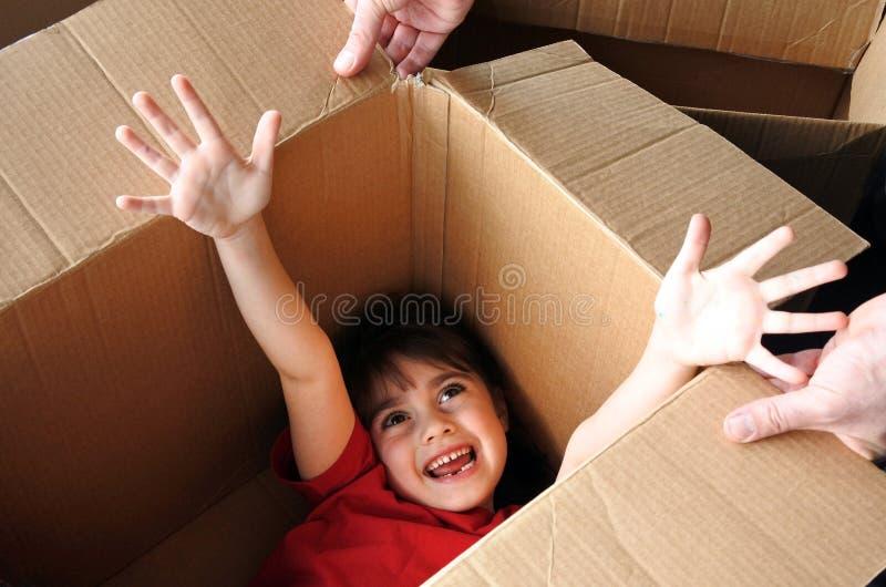 在搬入一新的hou的一个大纸板箱里面的愉快的女孩皮 免版税库存图片