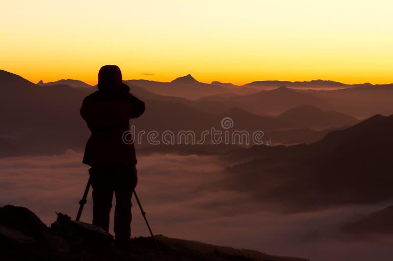 在摄影师剪影的有雾的山 免版税库存图片