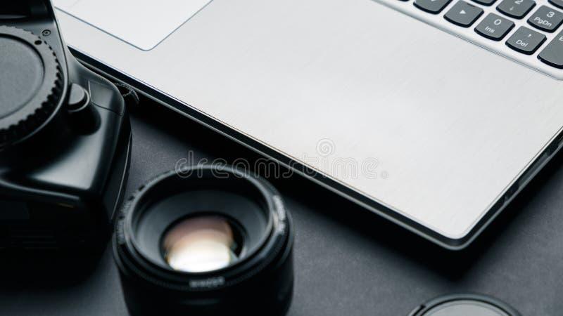 在摄影师黑桌上的工作区  免版税库存图片