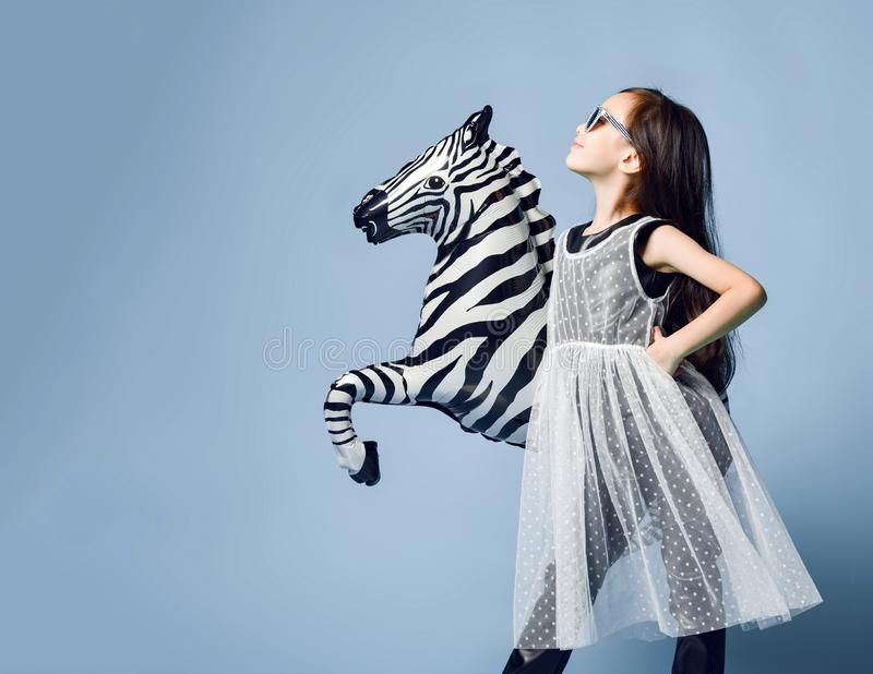 在摆在与斑马金属气球的外形的高档时尚衣裳和太阳镜的时髦的矮小的亚洲女孩孩子在薄荷脑蓝色 免版税图库摄影
