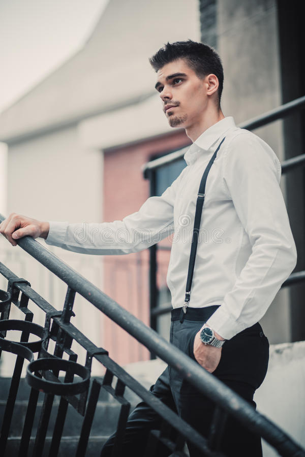 在摆在台阶附近的经典衣裳的年轻时髦的人模型 方式射击 库存图片