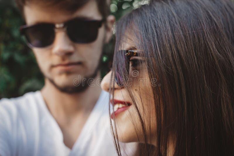 在摆在和做凉快的selfie的太阳镜的时髦的行家夫妇 在做自画象和拥抱的爱的幸福家庭夫妇 库存照片