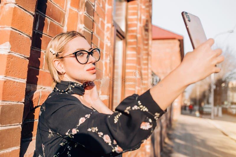 在摆在城市的礼服的美好的逗人喜爱的白肤金发的模型 免版税库存照片
