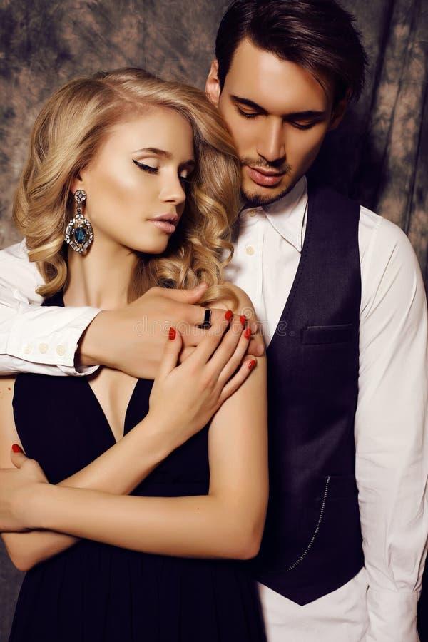 在摆在演播室的典雅的衣裳的美好的肉欲的夫妇 免版税库存图片