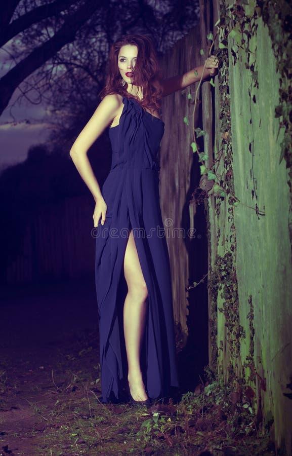 在摆在现代蓝色的礼服的时装模特儿户外 免版税图库摄影
