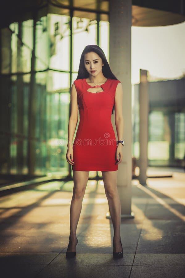 在摆在现代玻璃样式城市背景的红色礼服的美好的亚洲女孩模型 晴朗的日 库存照片