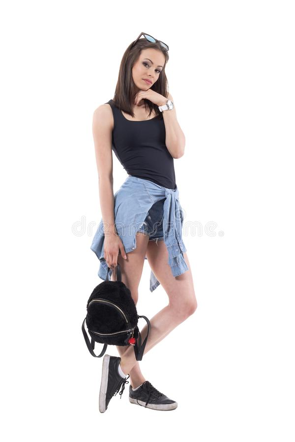在摆在用手的街道样式现代衣裳的时髦的深色的时装模特儿在下巴藏品袋子下 免版税库存图片