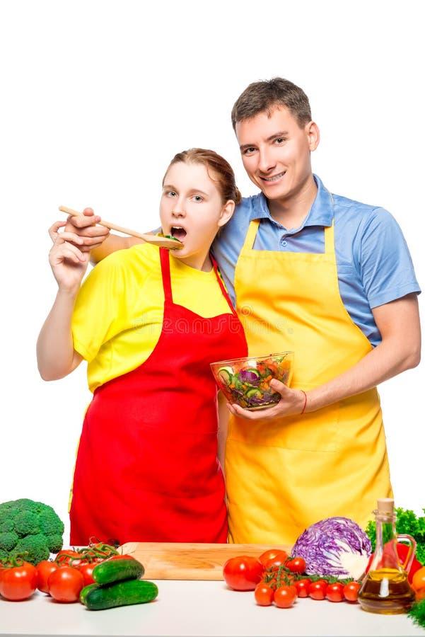 在摆在用菜沙拉的白色背景的年轻夫妇 库存照片
