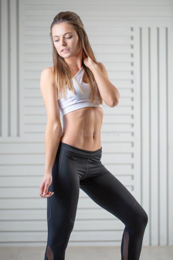 在摆在白色背景的运动服的可爱的年轻成人 有完善的身体的性感和肉欲的深色的妇女 免版税库存图片