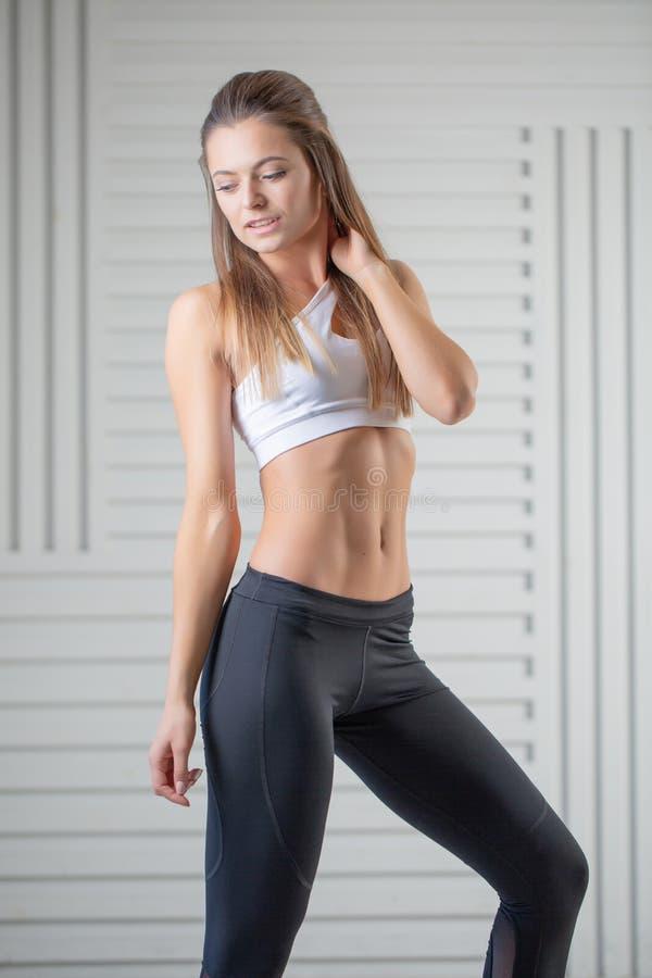 在摆在白色背景的运动服的可爱的年轻成人 有完善的身体的性感和肉欲的深色的妇女 库存图片