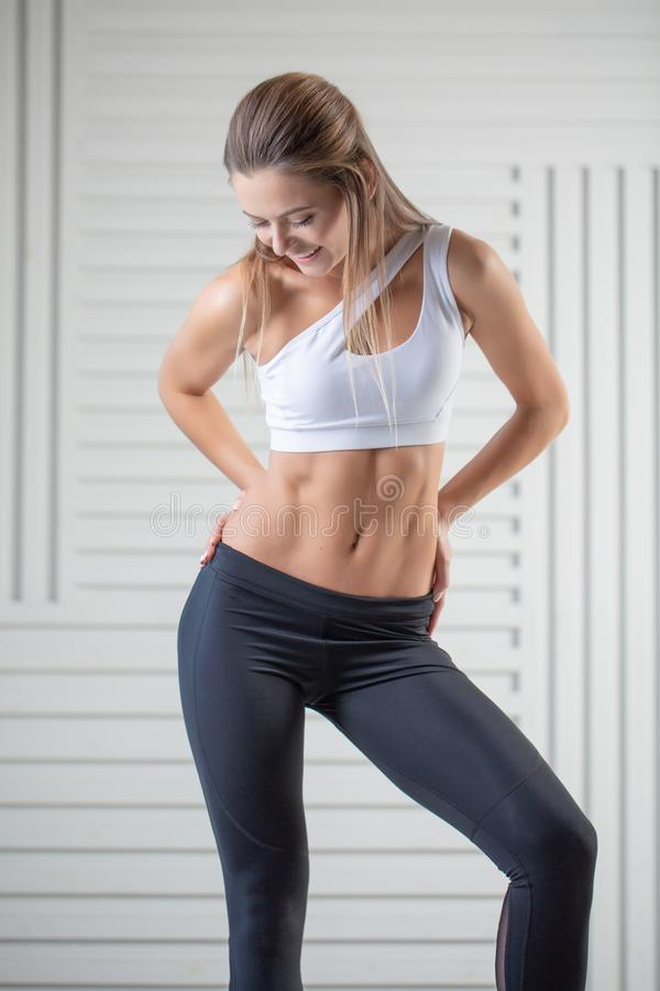 在摆在白色背景的运动服的可爱的年轻成人 有完善的身体的性感和肉欲的深色的妇女 图库摄影