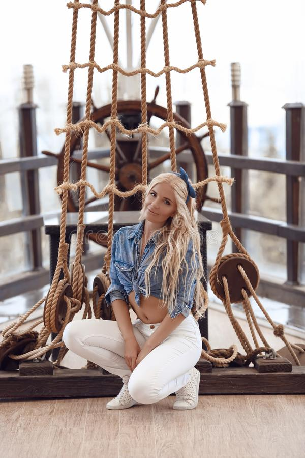 在摆在绳索的画报样式的秀丽时尚白肤金发的女孩模型 免版税库存照片